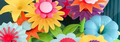 Child model's hand holding multi-colored plastic toy flowers