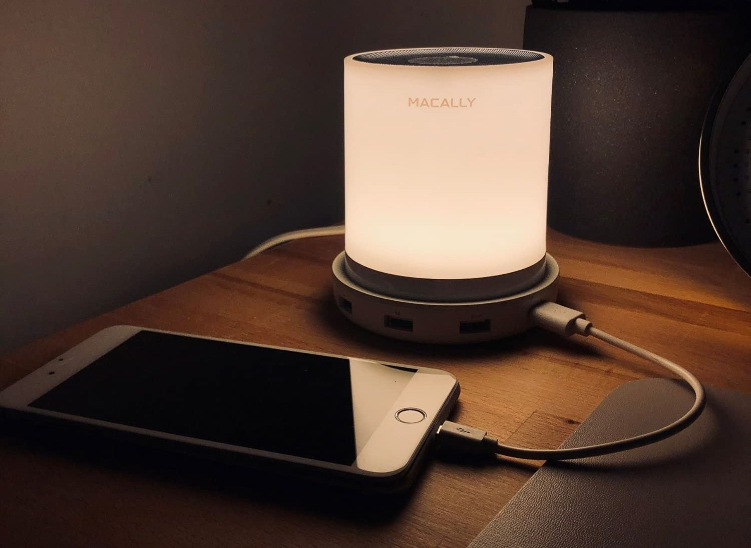 The light on a night table with a charging cellphone plugged in