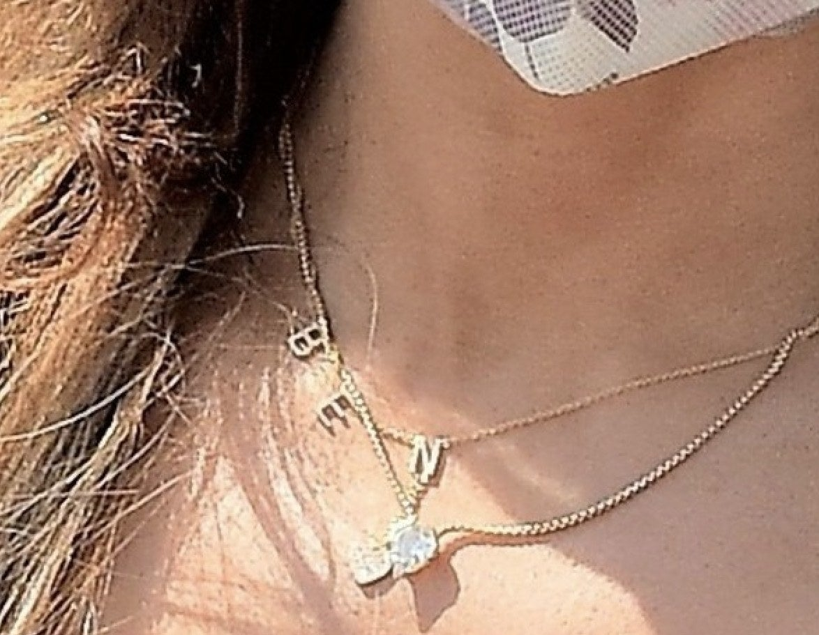 A zoom in on Jen's jewelry where a gold necklace that says BEN can be seen
