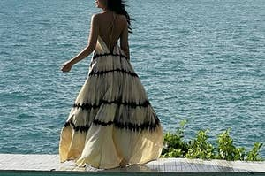 A model wearing the dress in beige next to a pool
