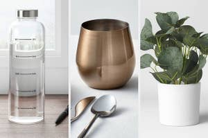 A water bottle on the left and a wine glass in the middle and a faux plant on the right