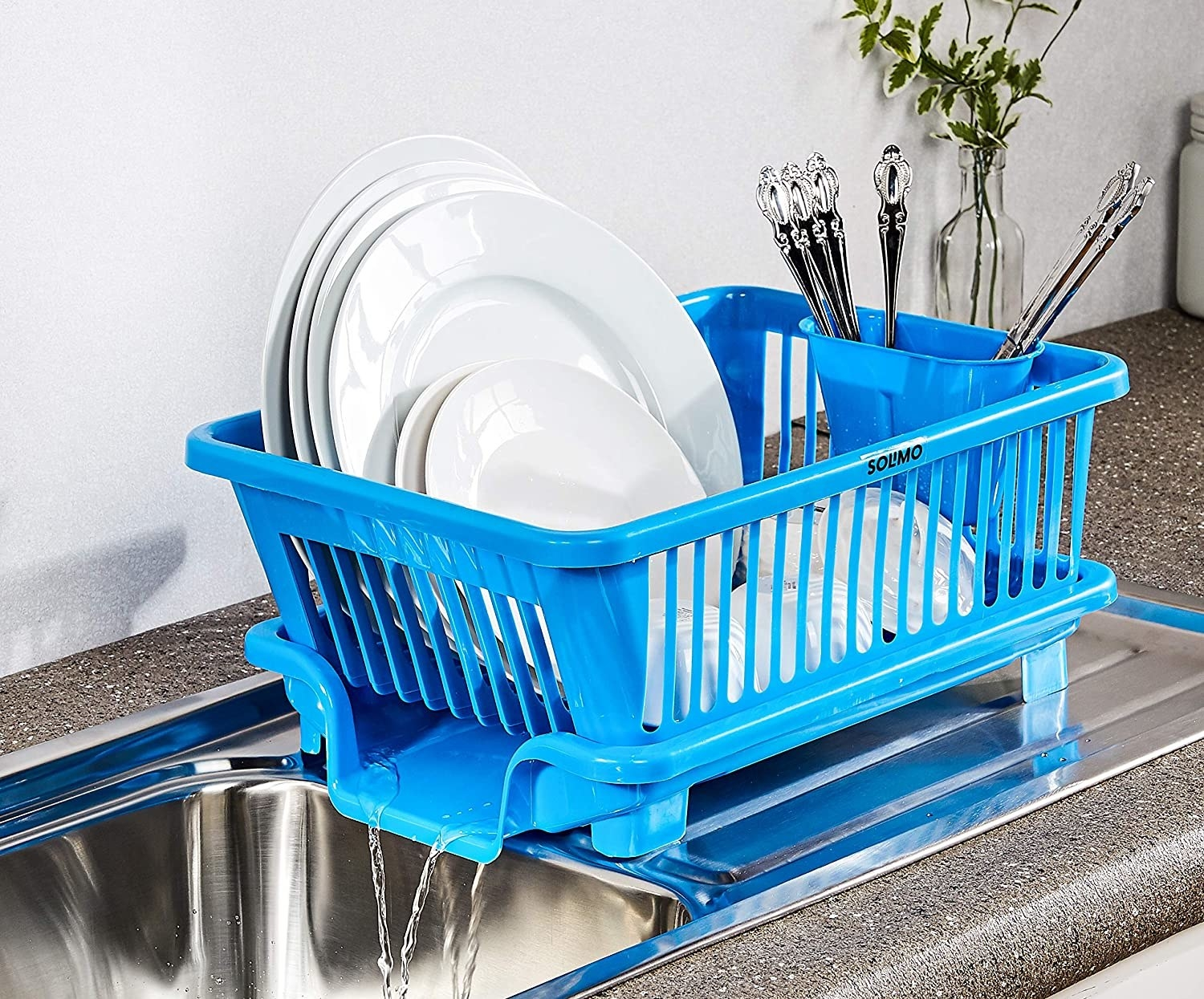 A blue dish drying rack with water running off from the side of it.