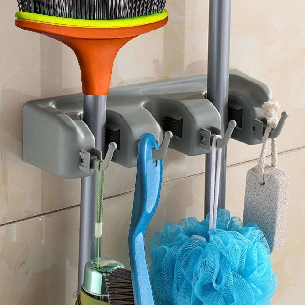 The wall-mountable stand with broom, brushes, mops neatly organized.