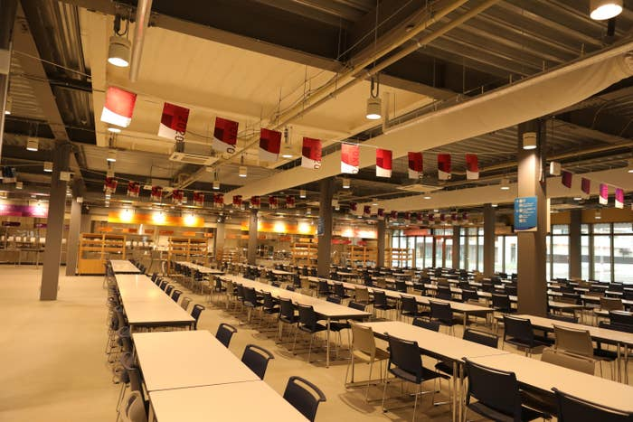A empty dining hall features rows of empty tables in a cafeteria setting