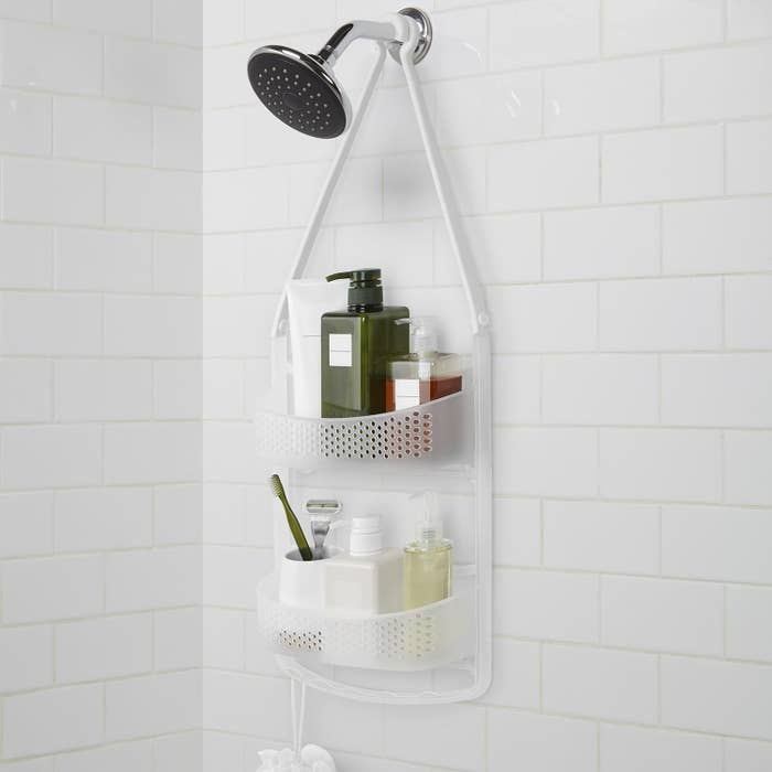 A shower caddy hanging from the shower head