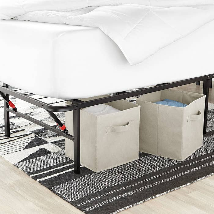 White foldable storage cubes stowed under a bed