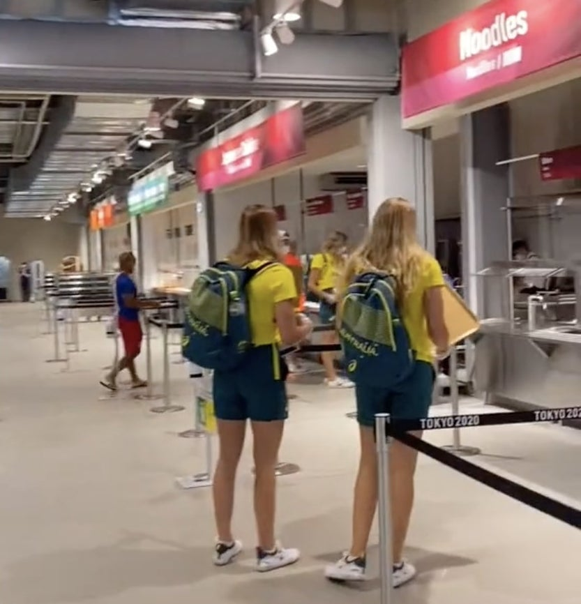 Two Team Australia members stand while waiting for their food
