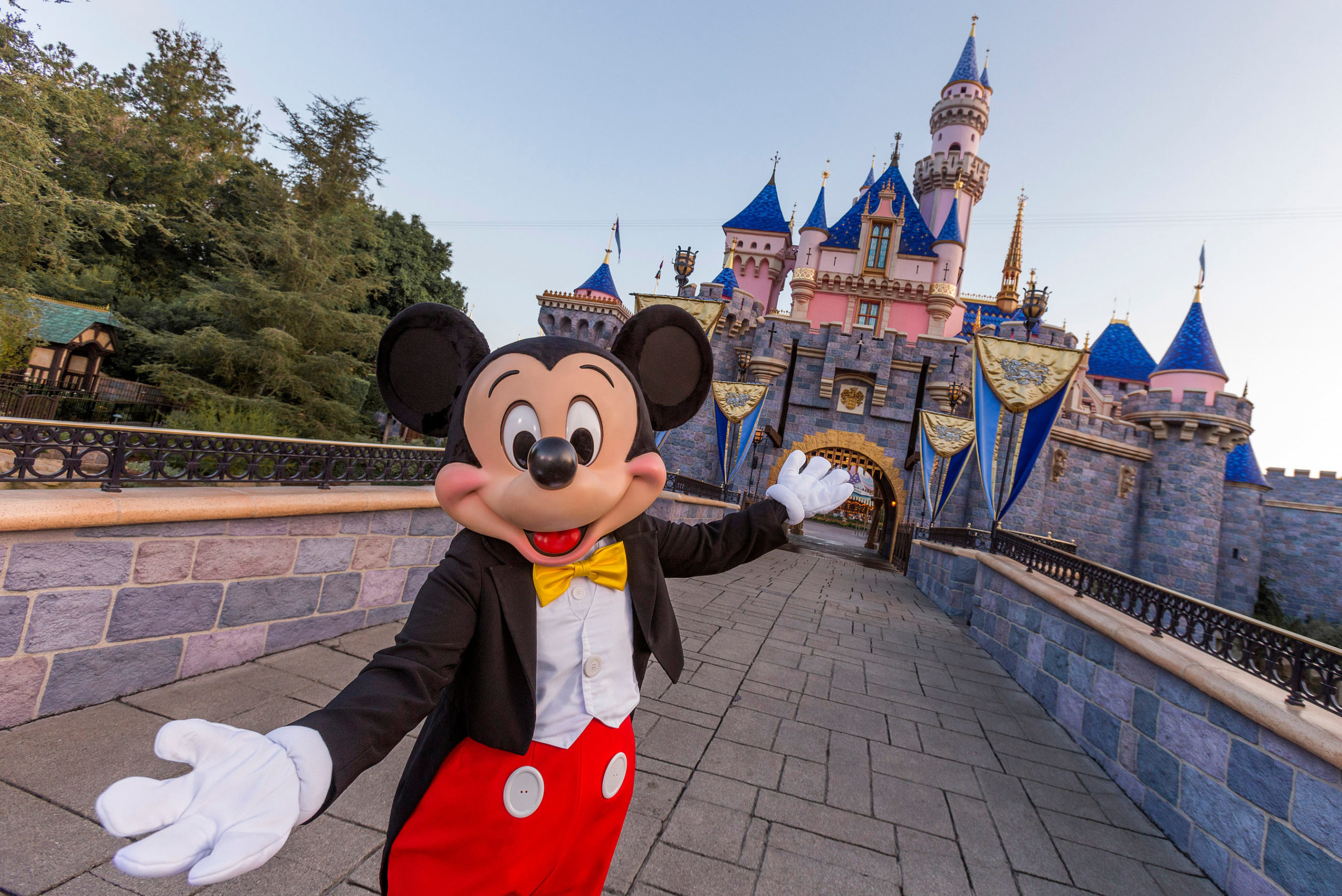 Mickey Mouse poses in front of Sleeping Beauty Castle at Disneyland Park