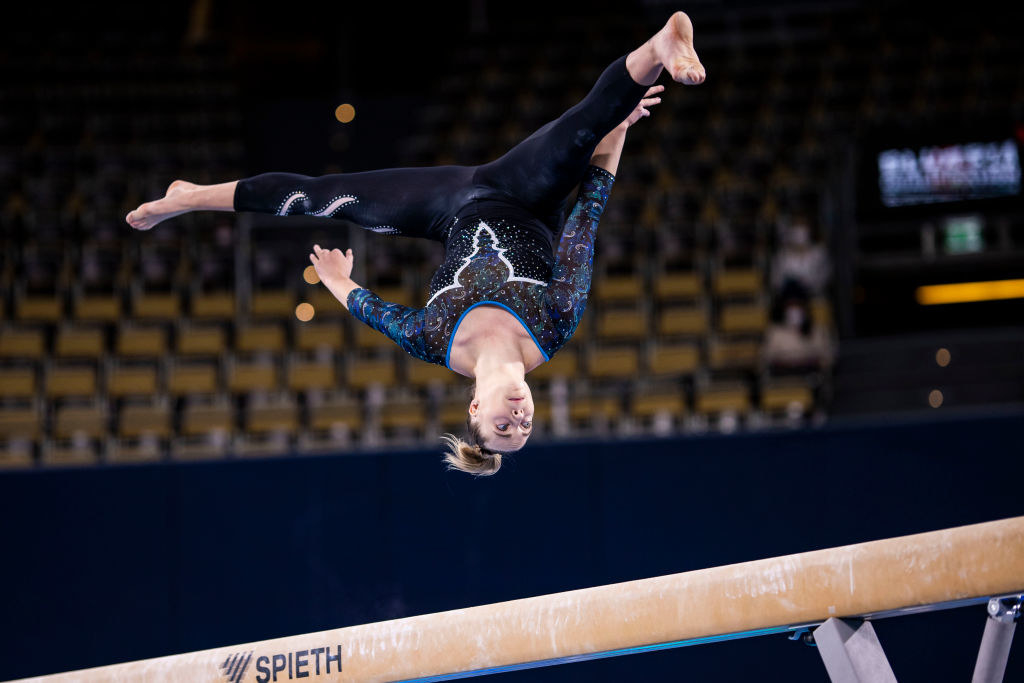 Carina Kröll wear a unitard while competing on beam