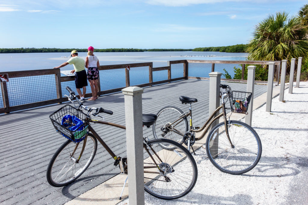 Two people looking out at water with two bikes parked on the pier behind them