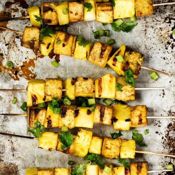 Charred skewers of tofu, scallions, cilantro, and pineapple