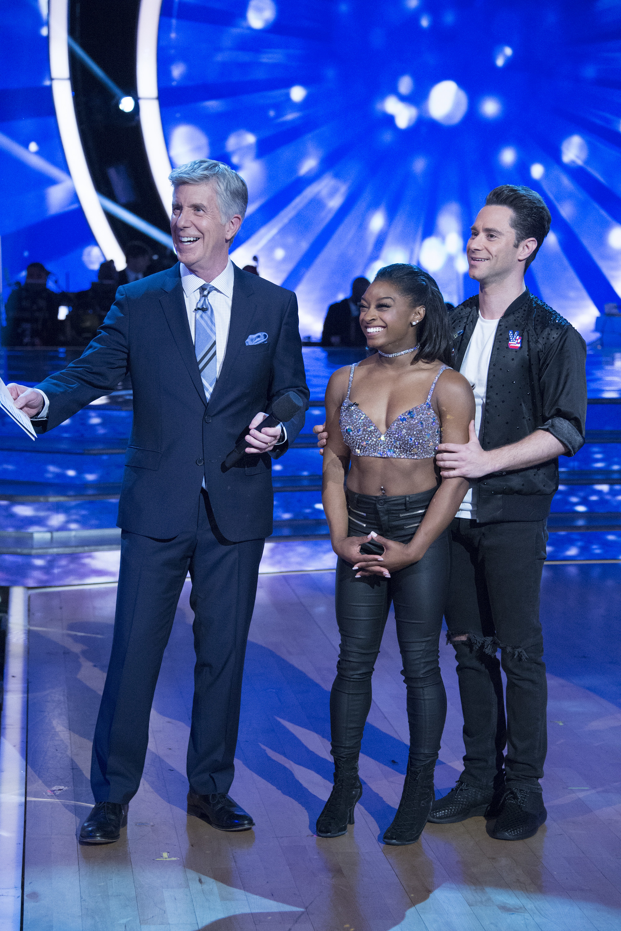 Simone waiting for her scores along with her dance partner and the host of Dancing with the Stars