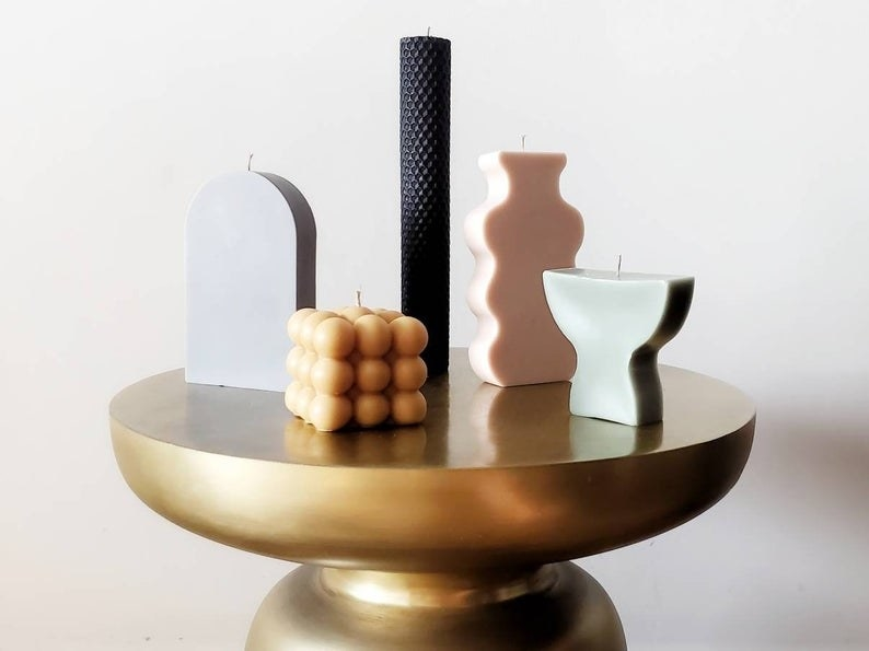 Several candles in geometric shapes and muted colors