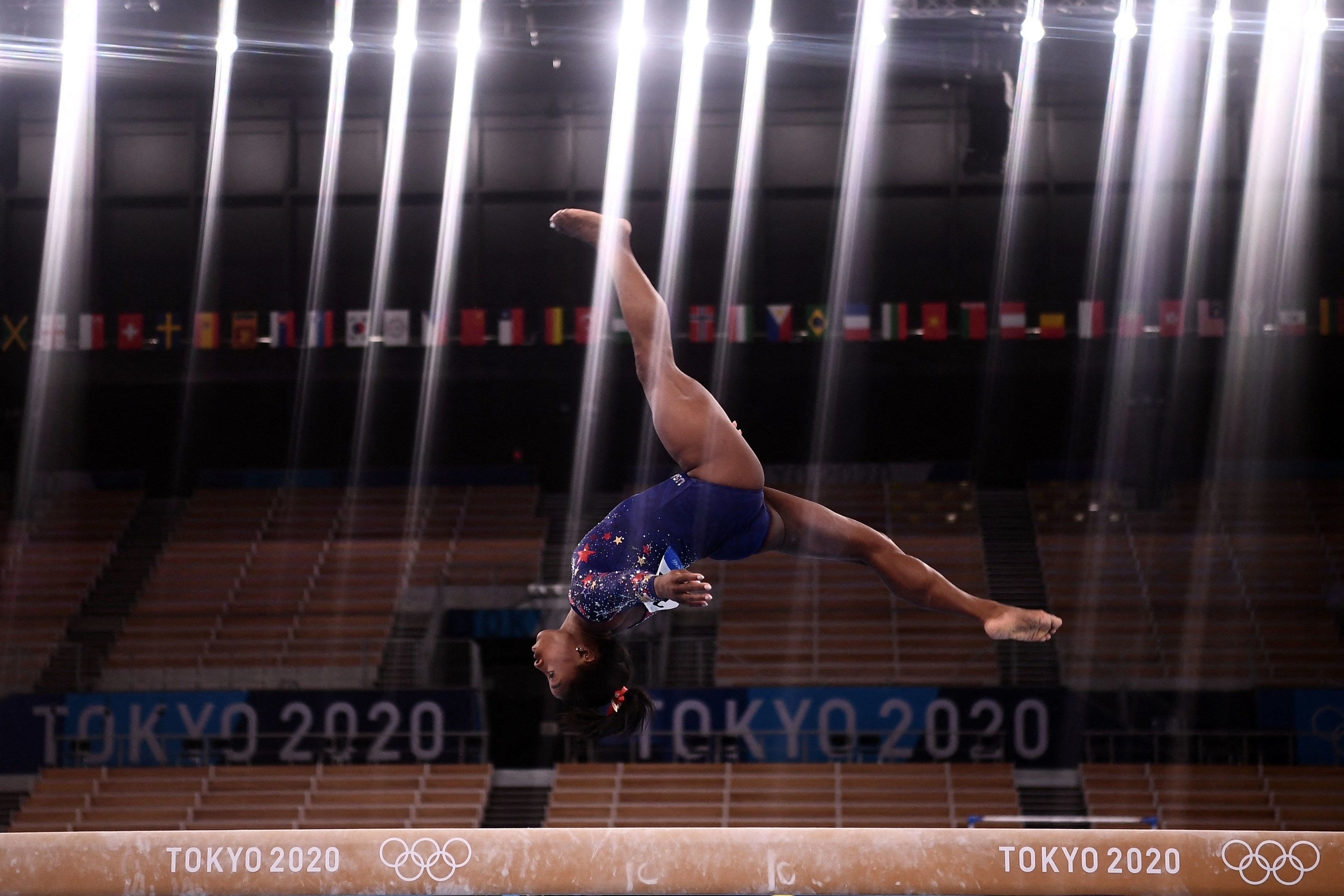 The overhead lights in the arena shining down as Simone flips over the balance beam
