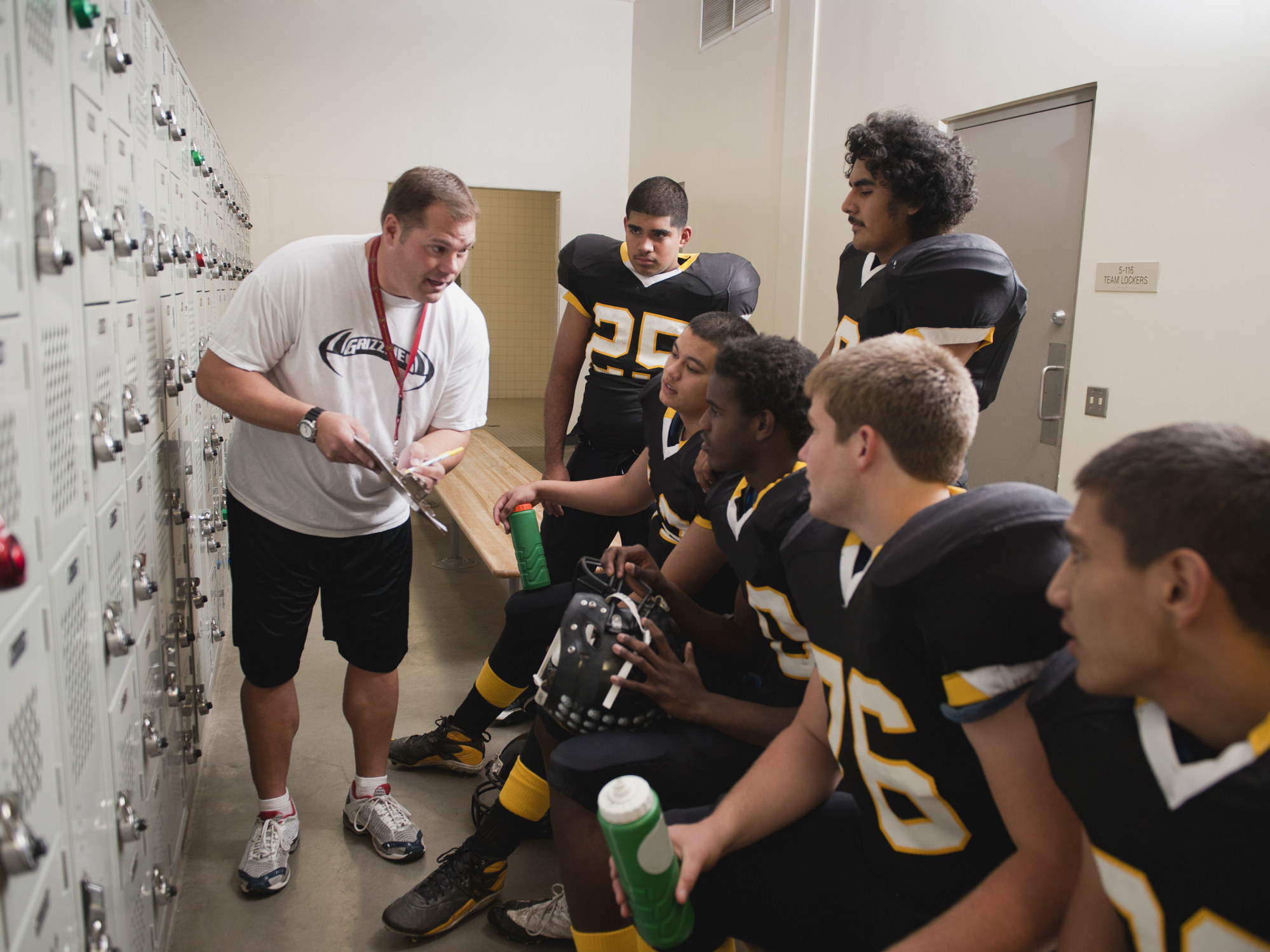 football coach with the team in the locker room