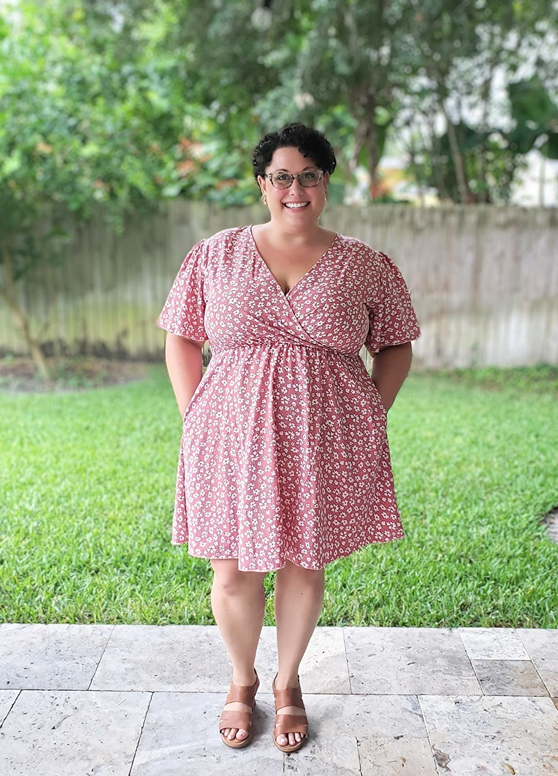 image of a reviewer wearing the pink and white floral v-neck wrap dress in a size 20 plus