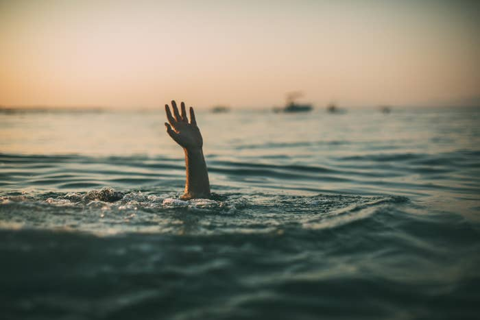 A person reaching their hand above water for help