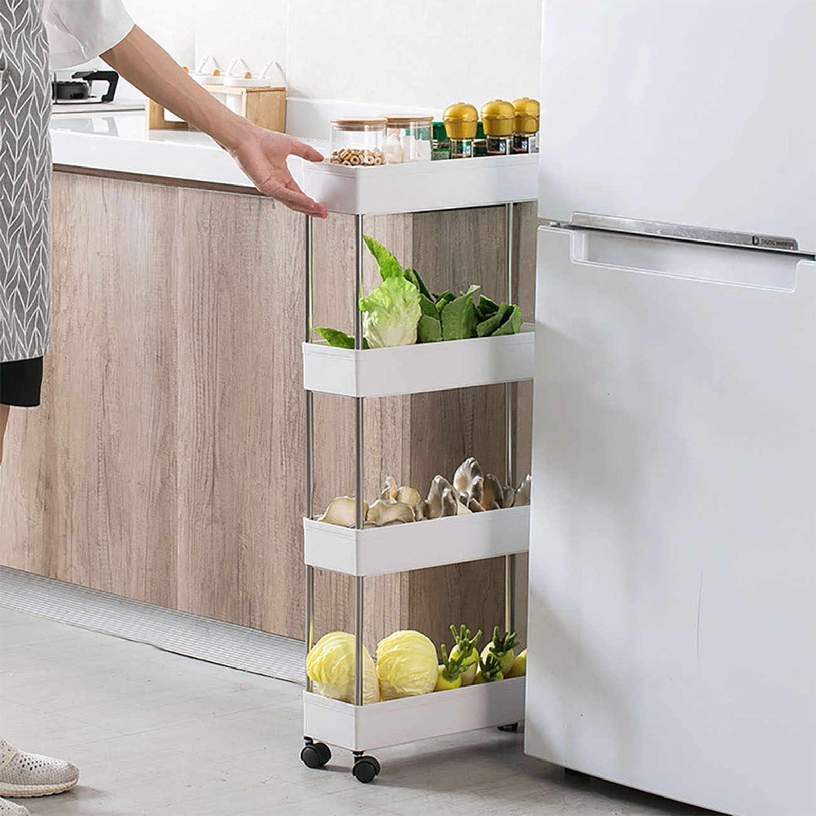 close up of a model pulling the 4-tier narrow sliding cart from between a fridge and countertop