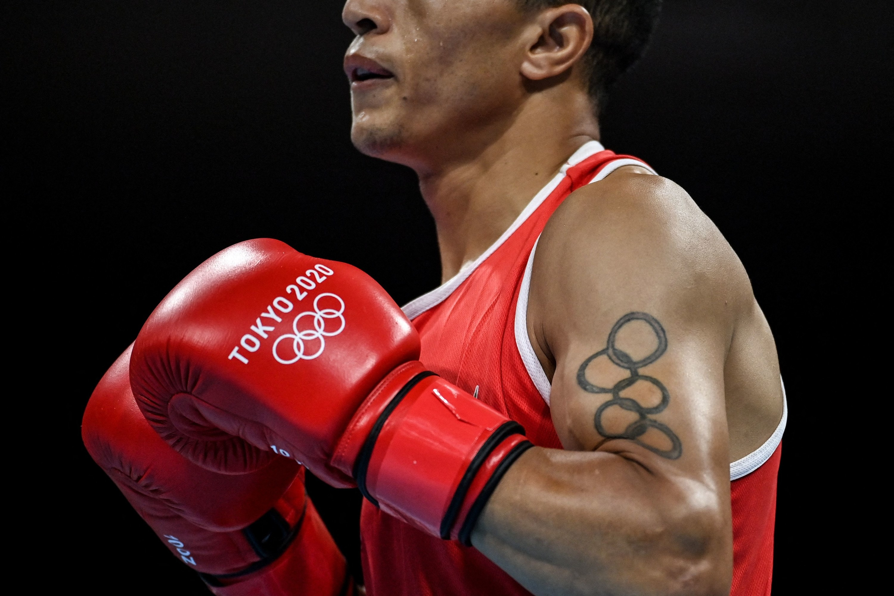 Olympic boxer wears red Tokyo 2020 gloves and flexes before competition