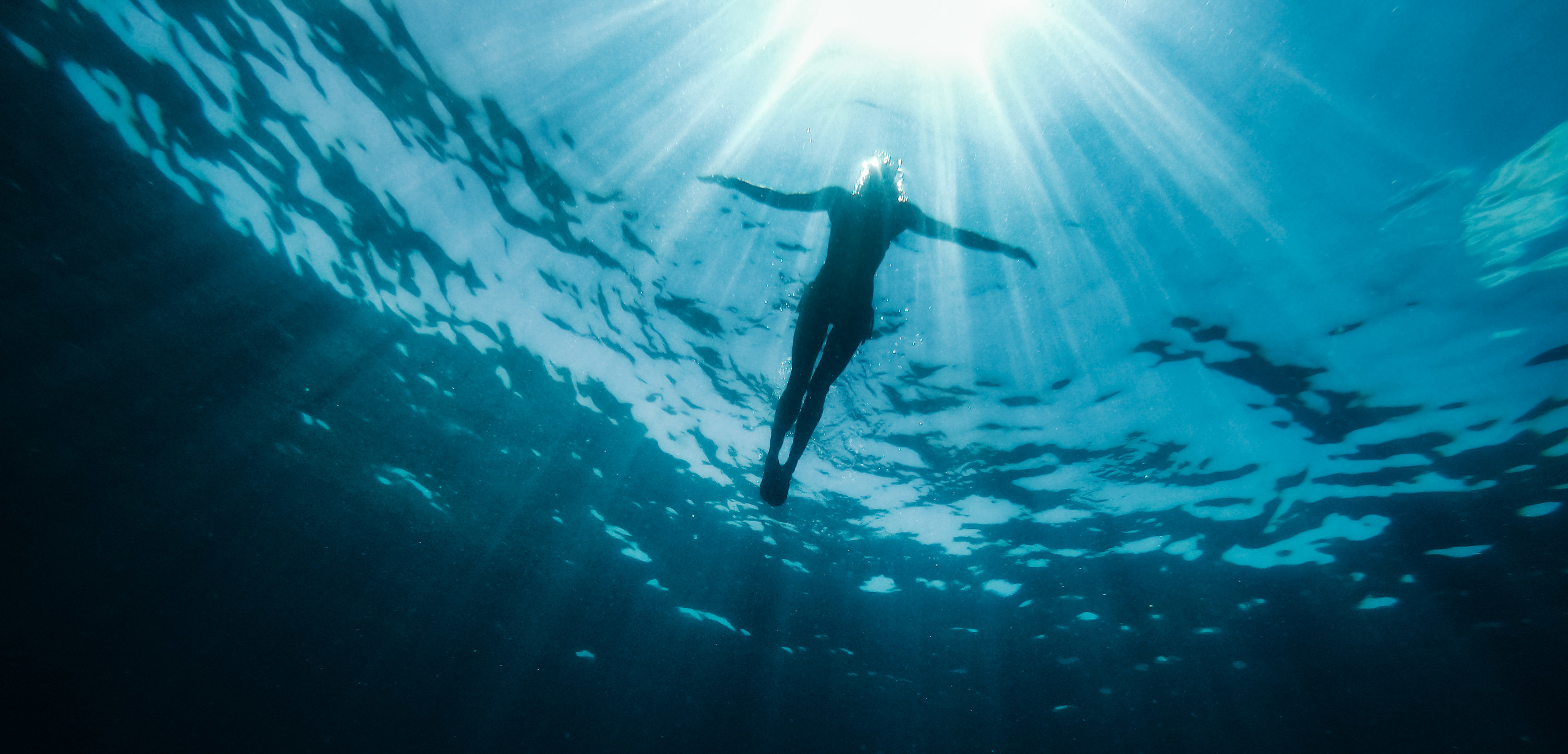 Underwater photo of woman floating in the sea and rays of light piercing through
