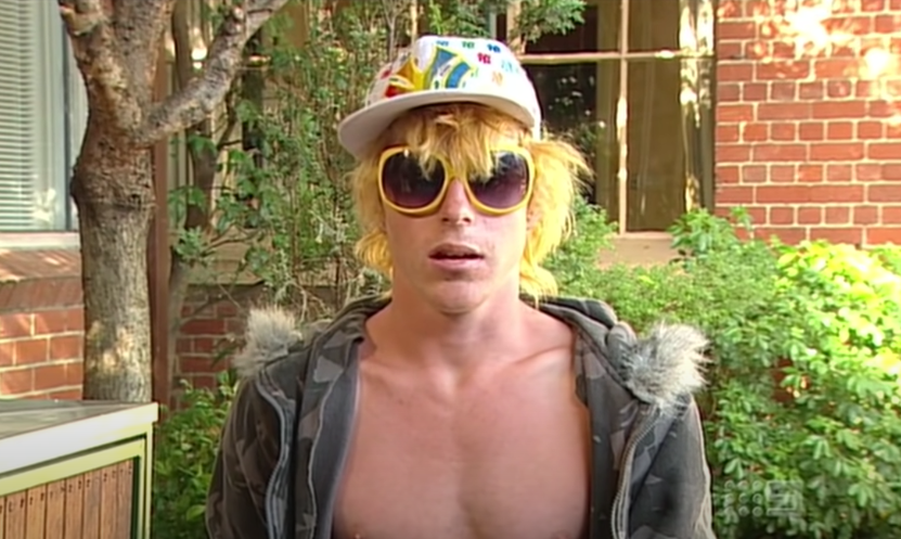 A bleach blond young guy in yellow sunglasses, colorful baseball cap, and wearing a hoodie with no shirt on