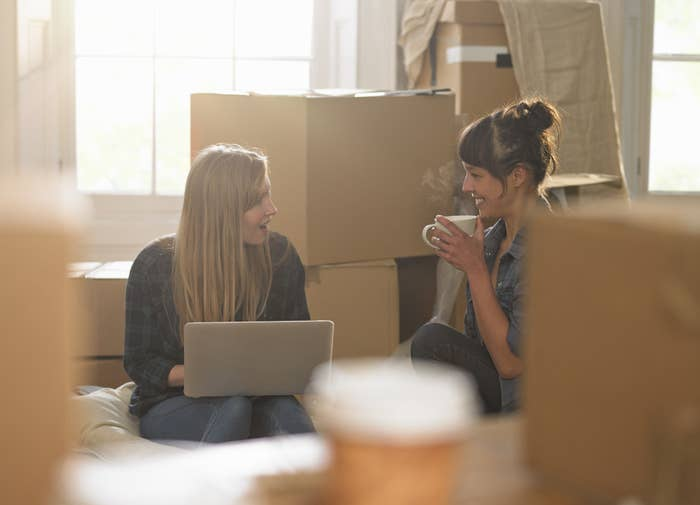 Young roommates surrounded by boxes in their new apartment