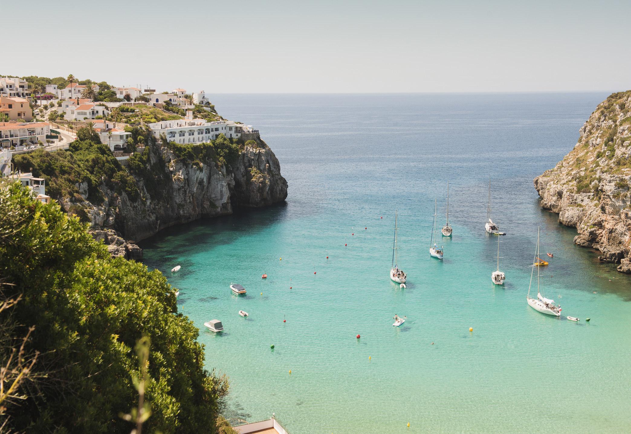 Boats in the serene blue water in Menorca.