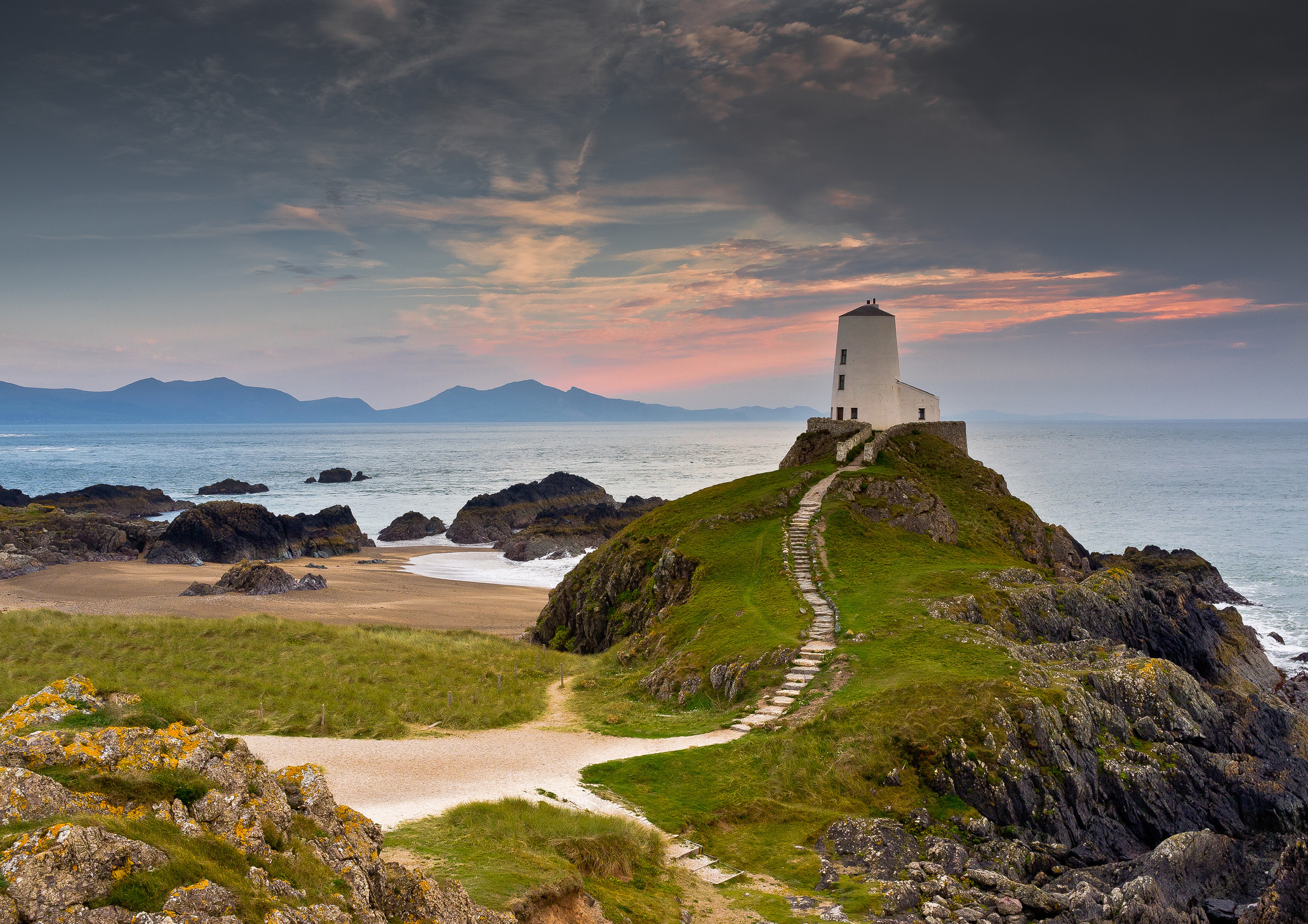 Llanddwyn Lighthouse with Snowdonia mountains in the backdrop.