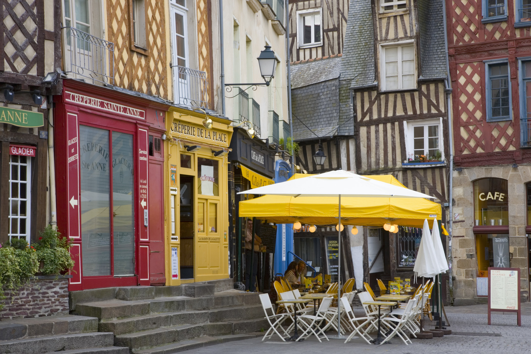 Colorful buildings and a cafe in a square in Rennes, France.