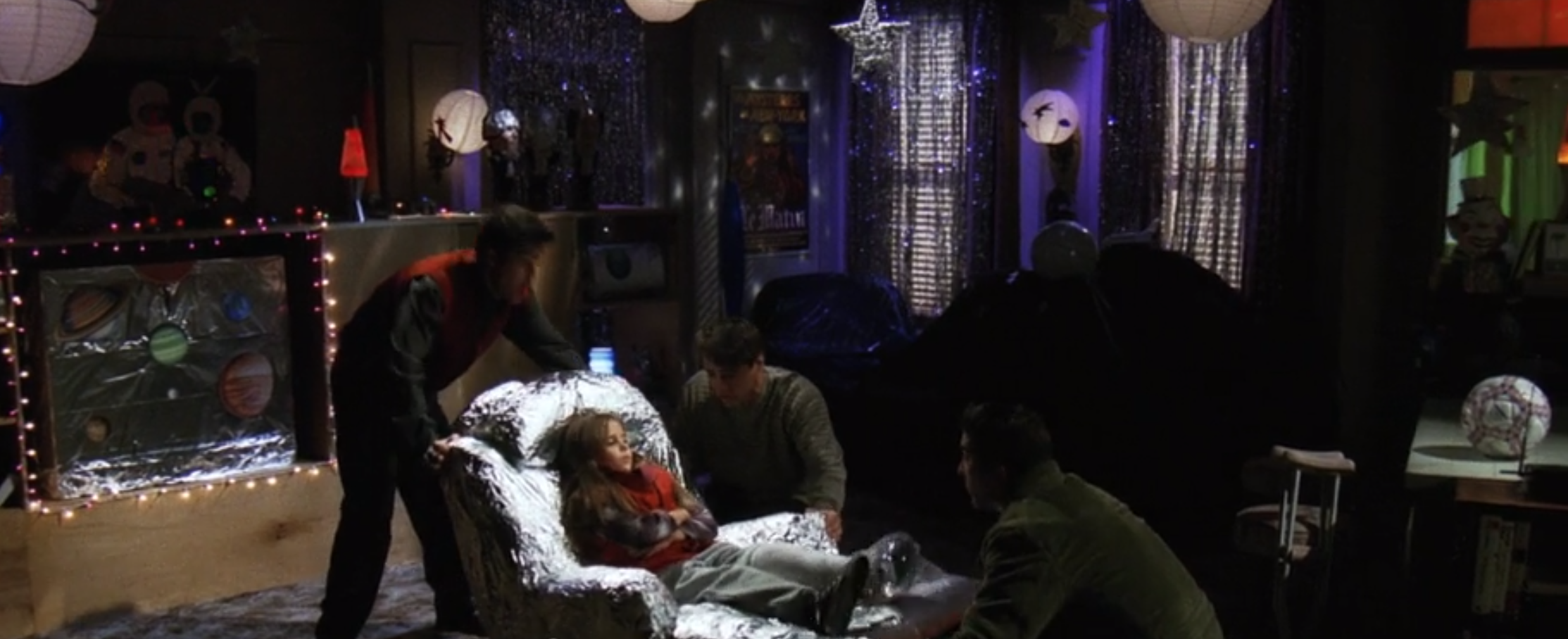 Chandler, Joey, and Ross help a little girl into a tin foil covered arm chair