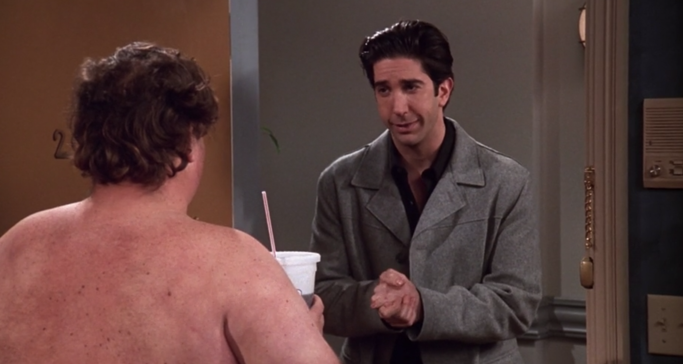 Ross stands with his hands clasped together in front of a naked man holding a soda cup