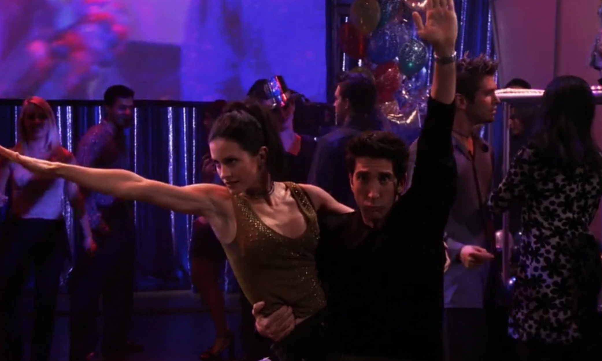 Monica poses with her arm outstretched as she's picked up by Ross who has one arm in the air