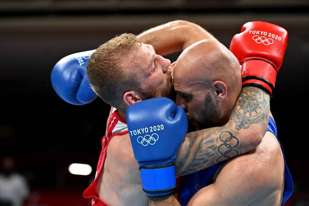Two Olympic athletes compete in a boxing match in Tokyo.