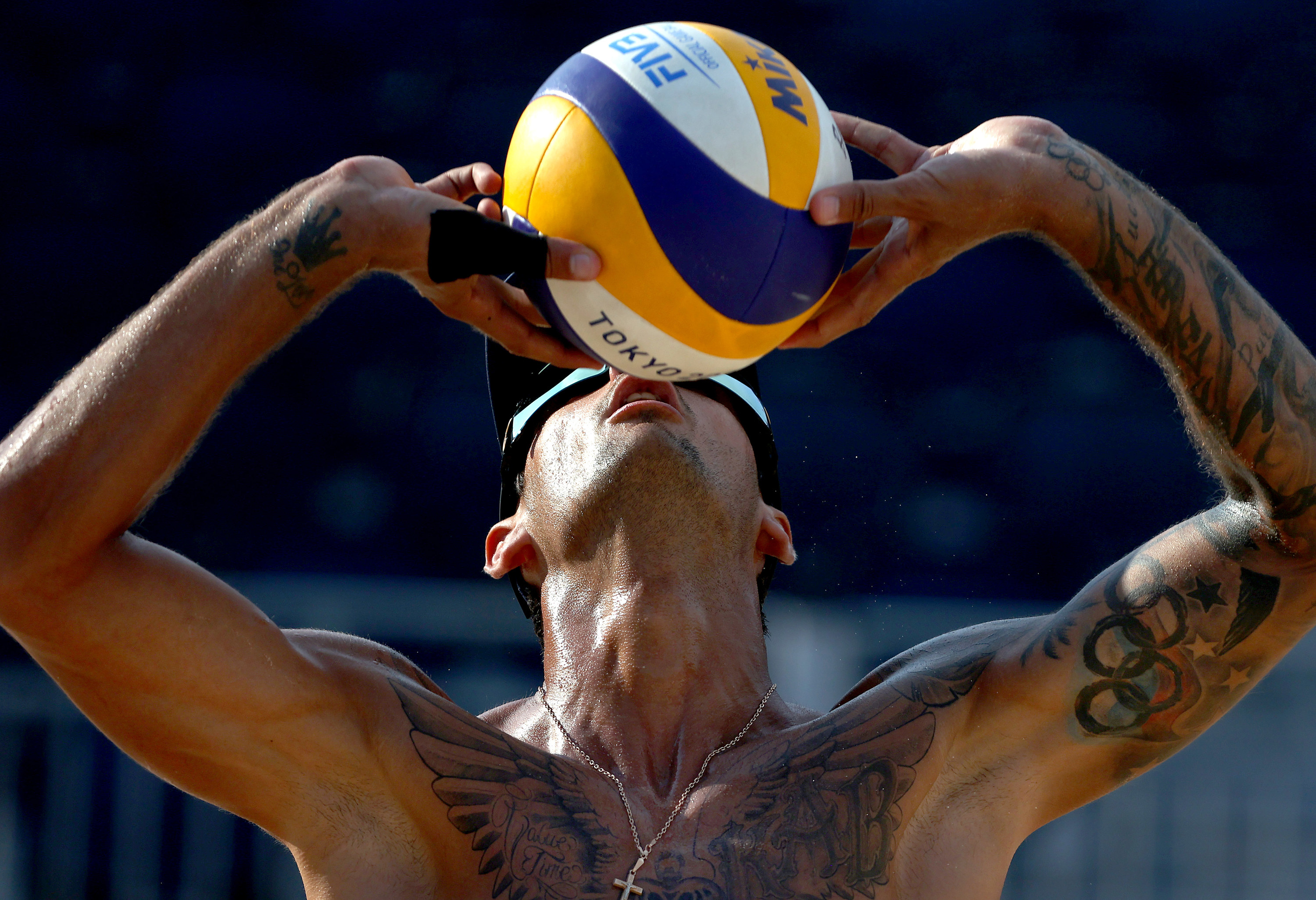 A tattooed volleyball player seen practicing for a match.
