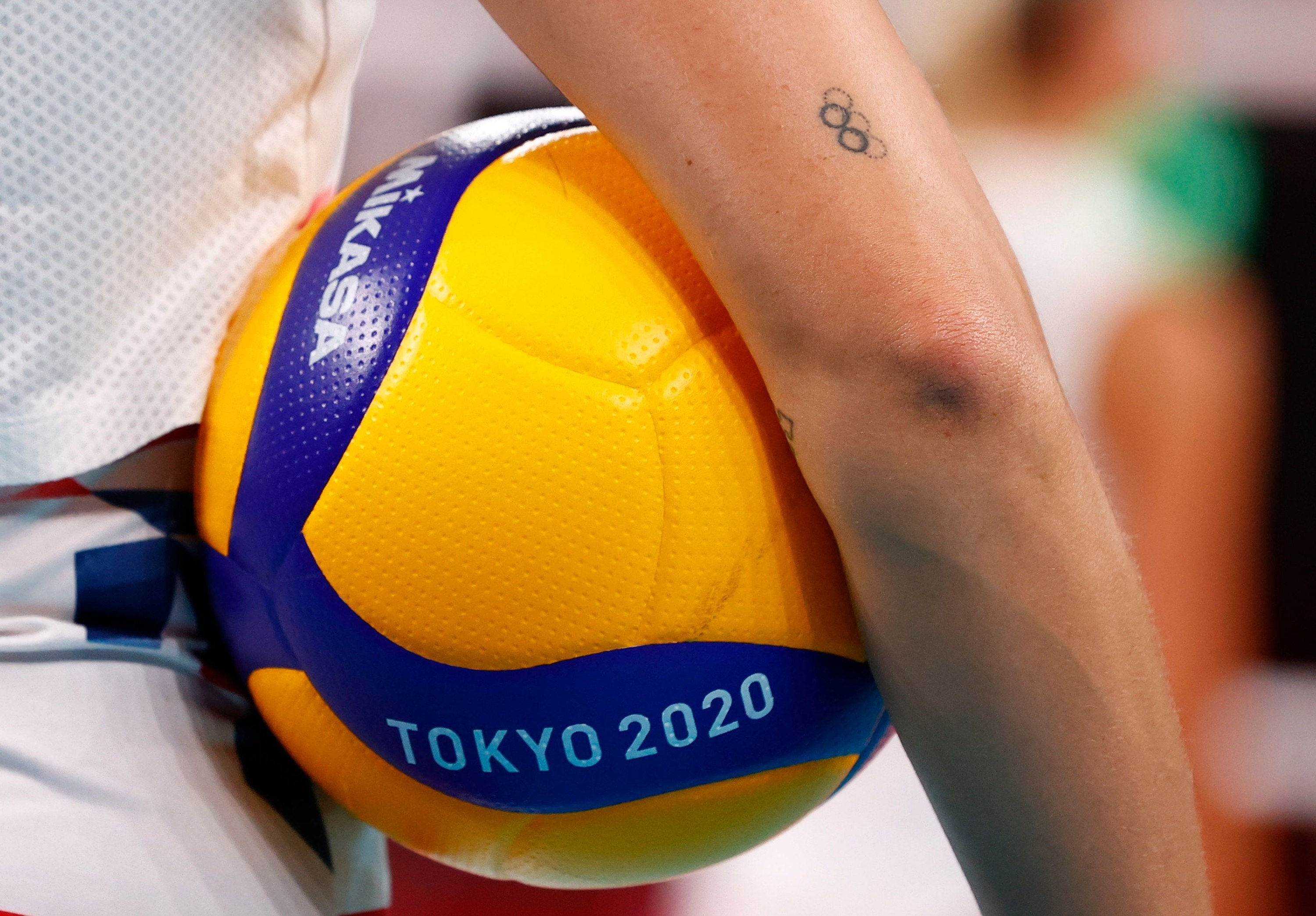 Bright yellow Tokyo 2020 ball is held under the arm of an Olympic athlete