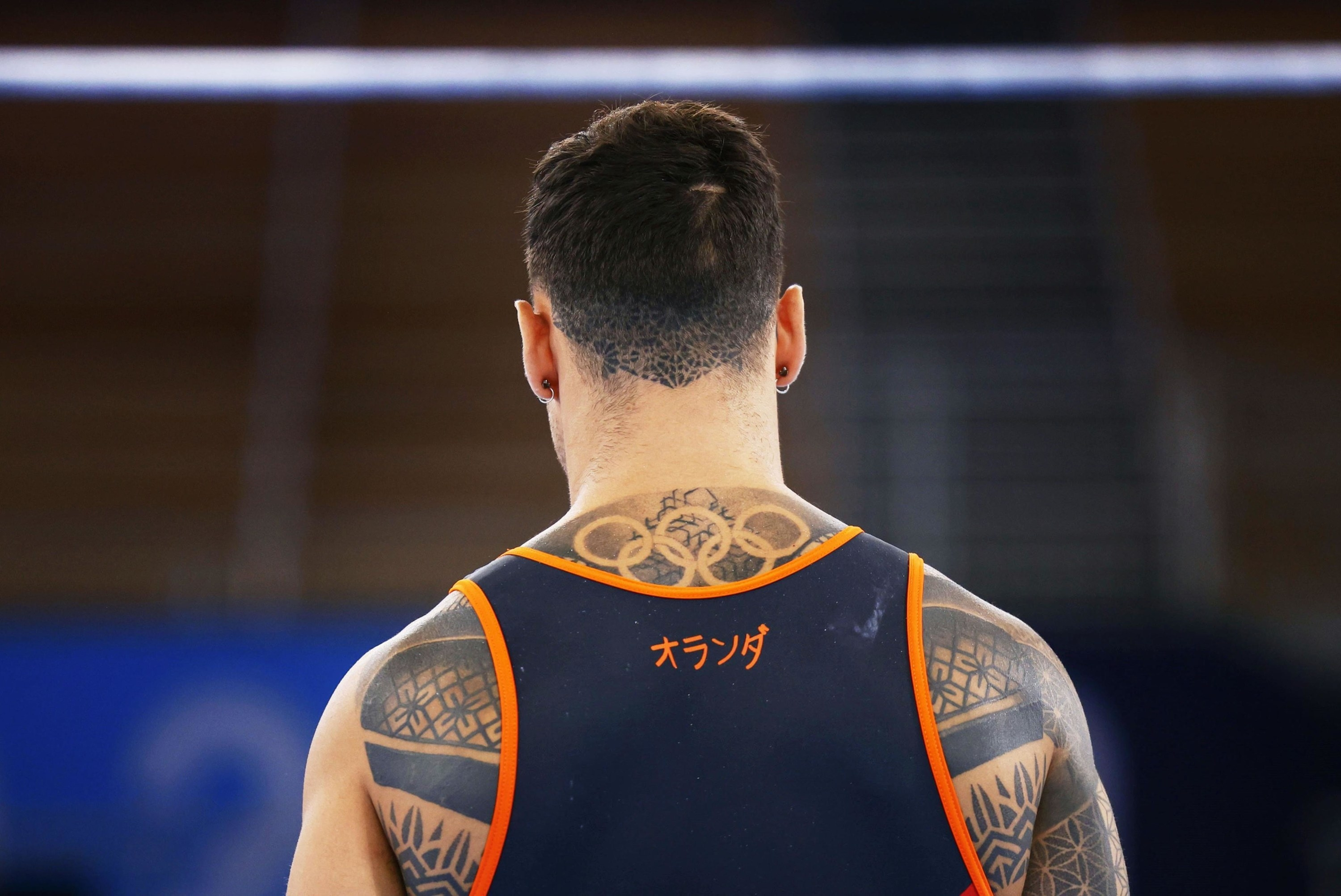 Back view of a male gymnast's tattoos.