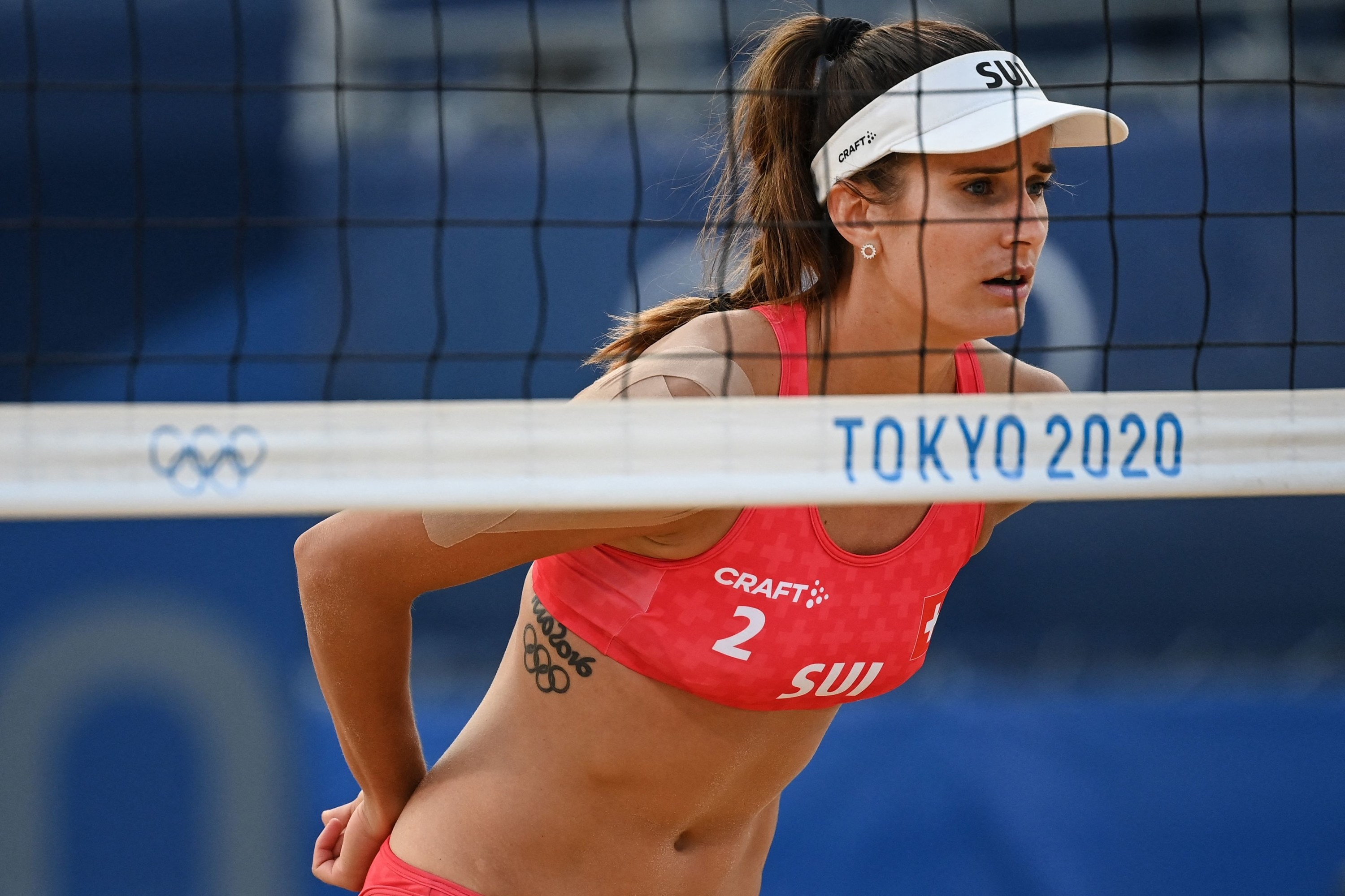 Olympic volleyball player stands close to the net during a match.