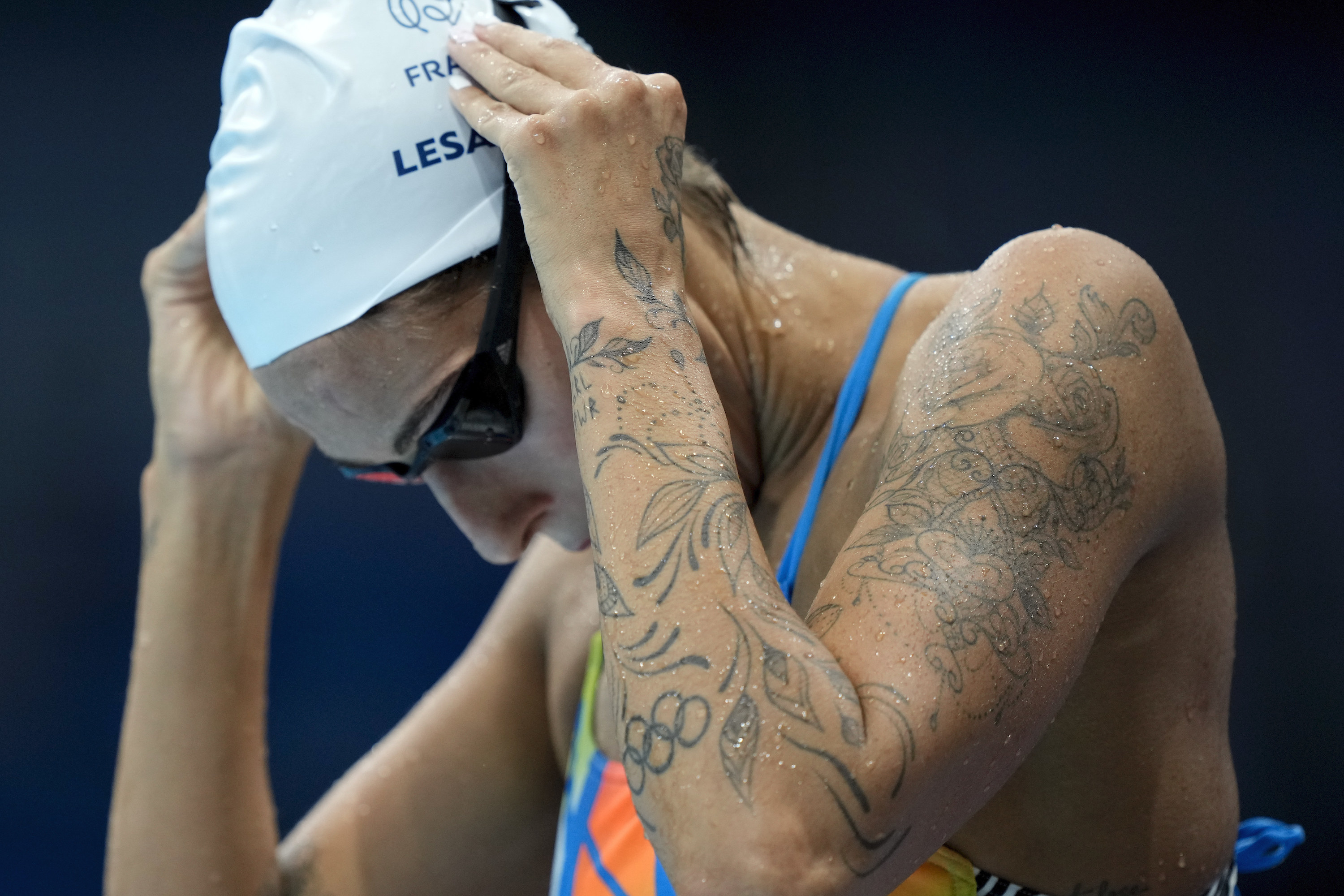 Female Olympic swimmer's arm shows dainty tattoos
