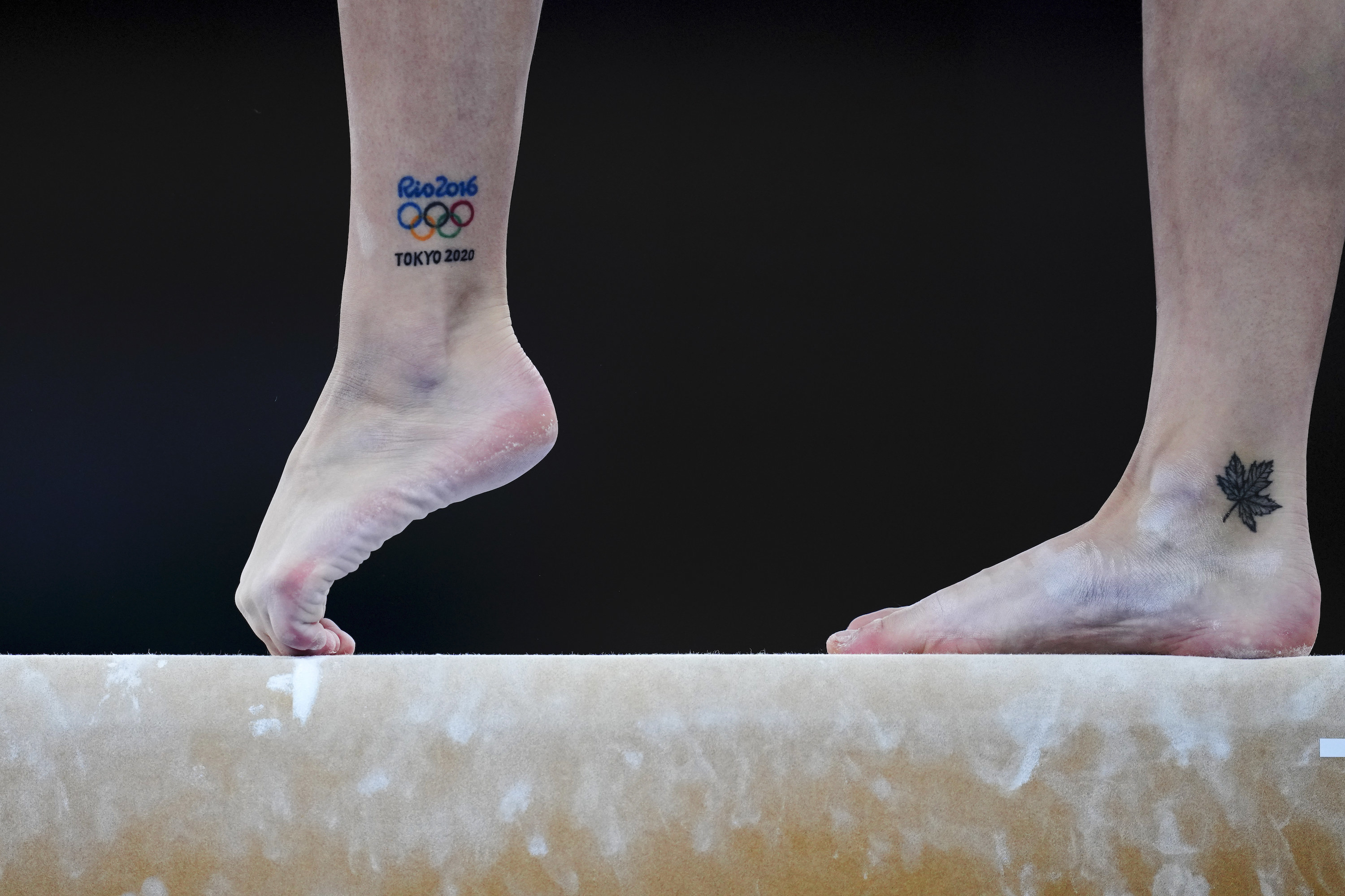A gymnast's pointed foot on the balance beam with the Olympic rings tattooed on ankle