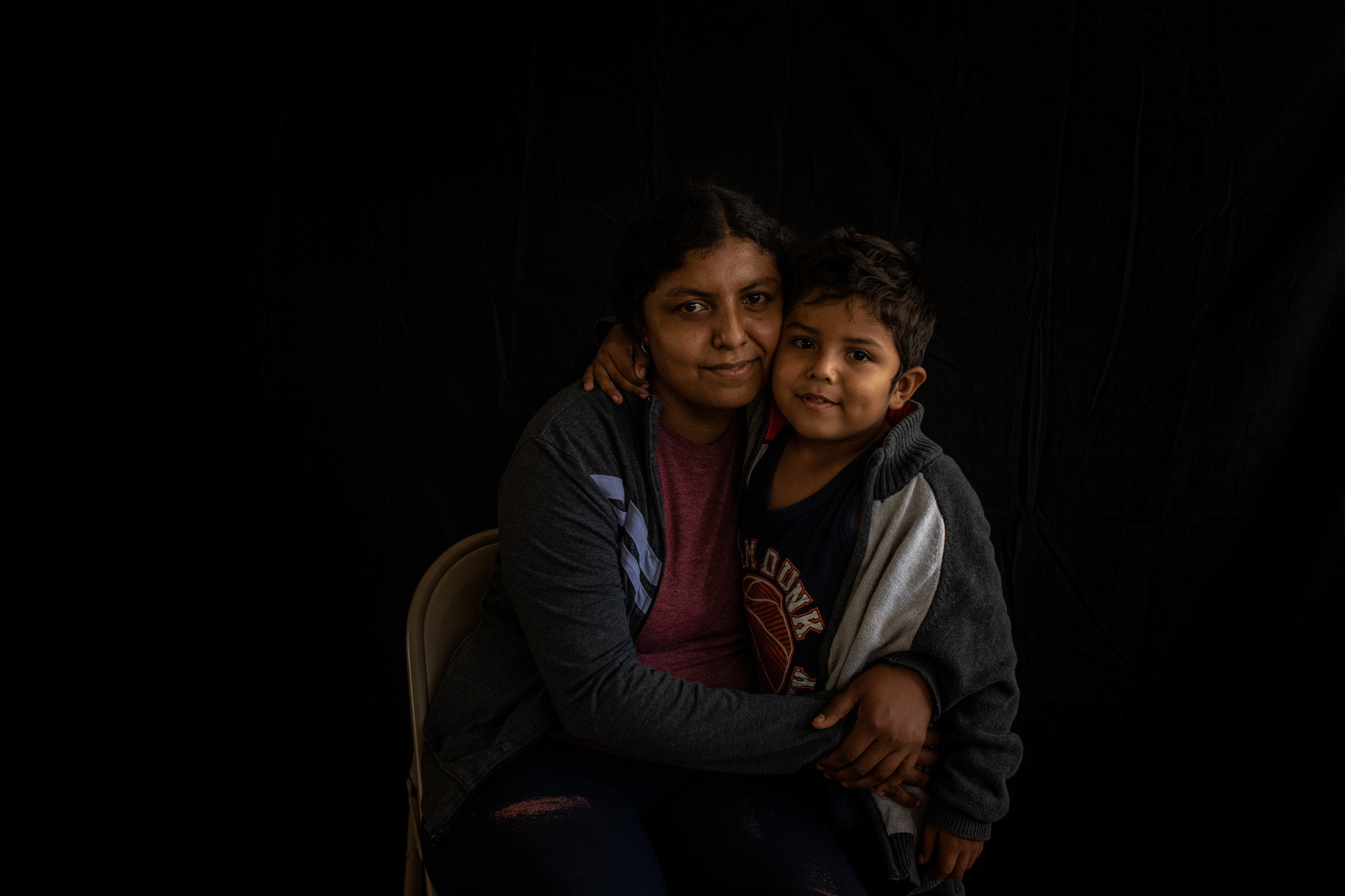 A migrant mother and son sit on a folding chair on a black background, embracing and looking at the camera