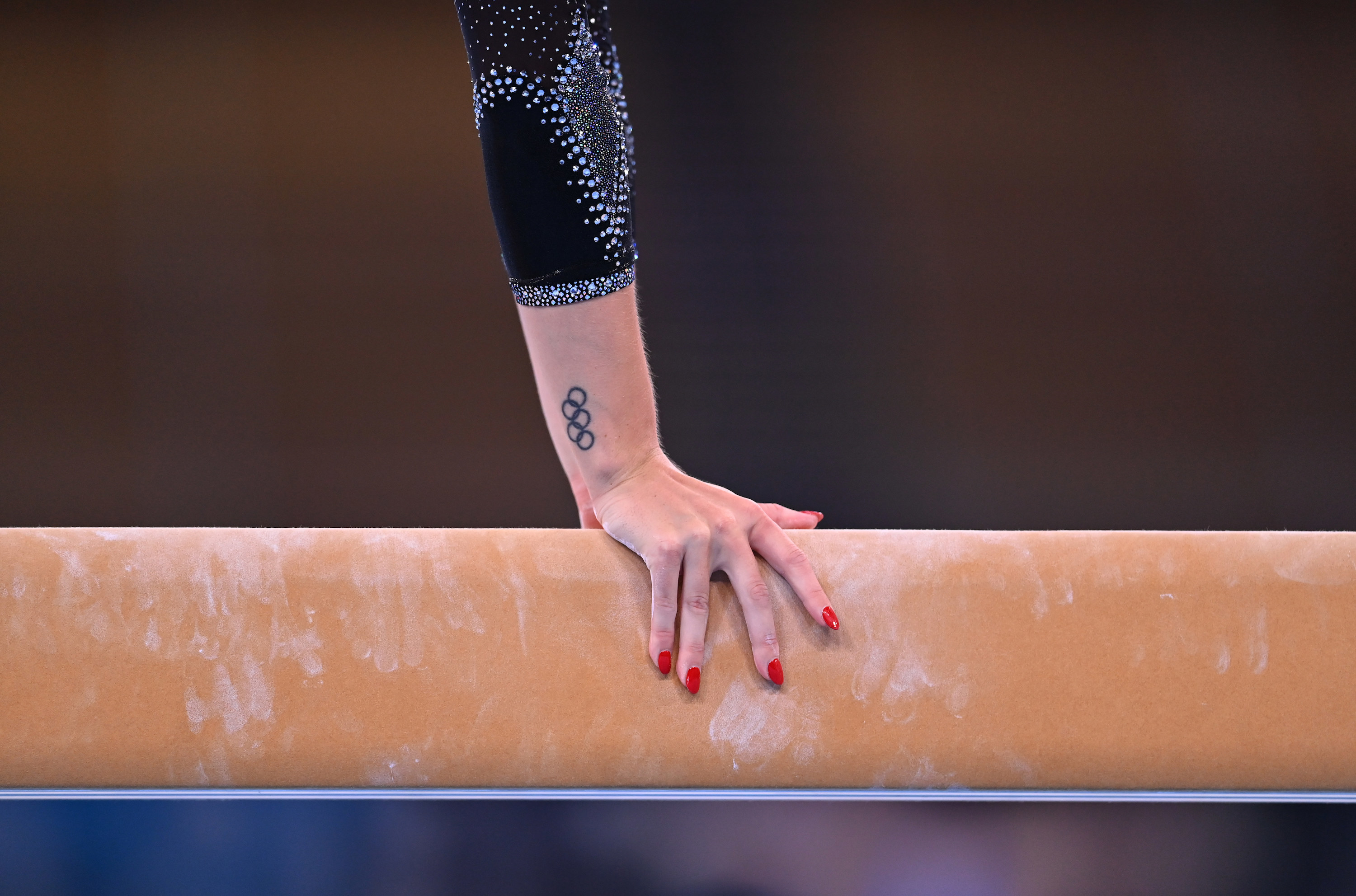 Gymnast's hands on the balance beam with red nails and Olympic rings tattoo