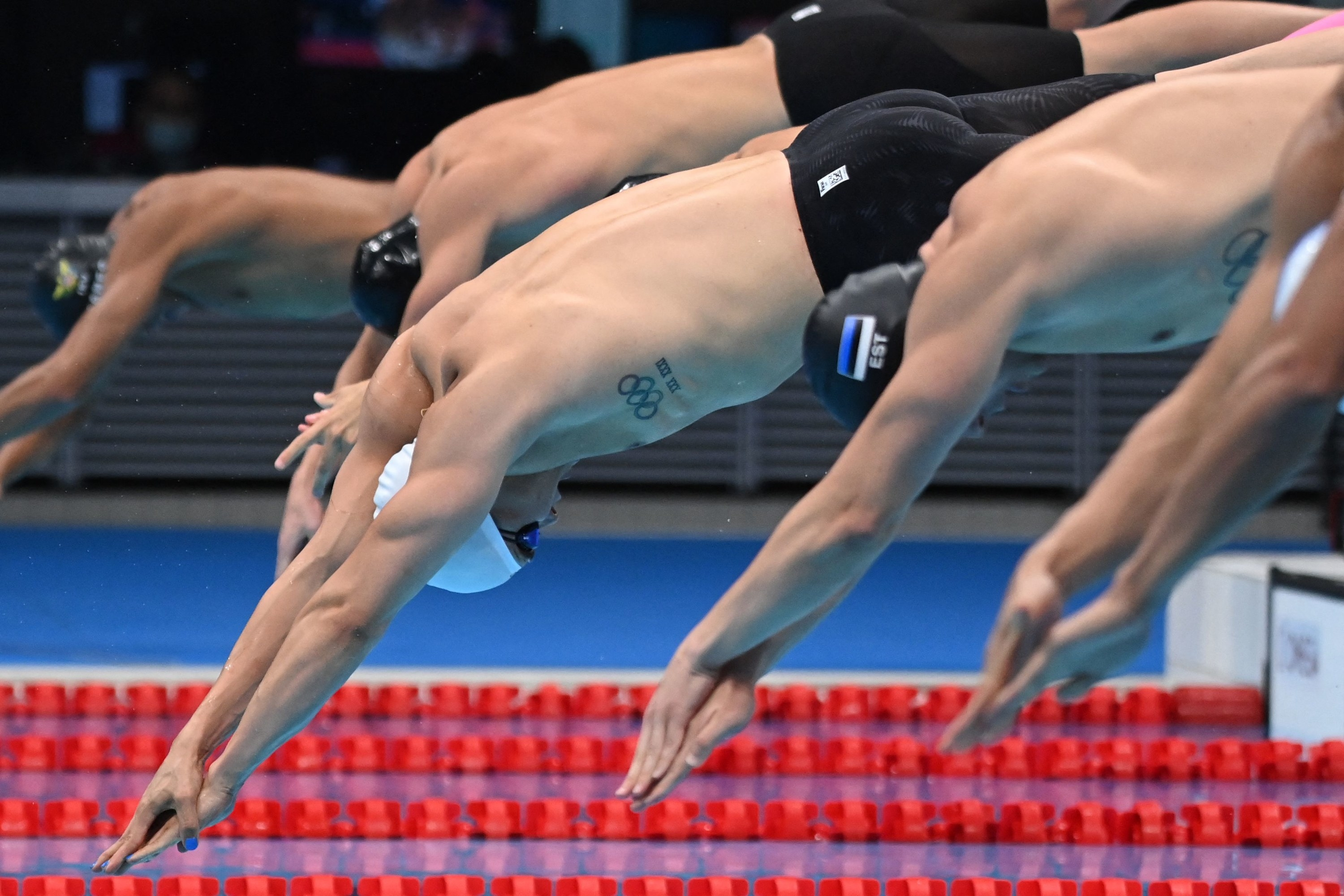Group of male swimmers dive into Olympic pool at start of competition