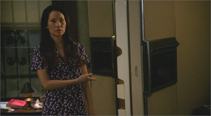watson wears a dress, stands in front of open door, pointing to door