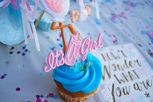 """Cupcake with blue frosting and decoration that says, """"It's a girl."""" Napkin next to it says, """"How I wonder what you are."""""""