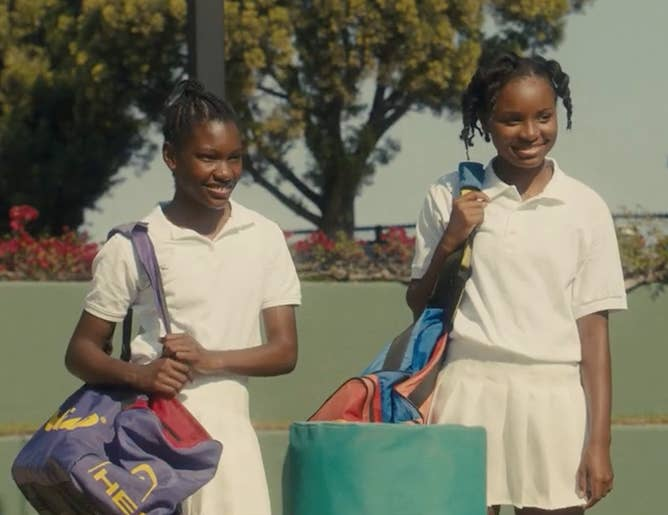 Demi Singleton as Serena Williams and Saniyya Sidney as Venus Williams, dressed in tennis clothes on a tennis court