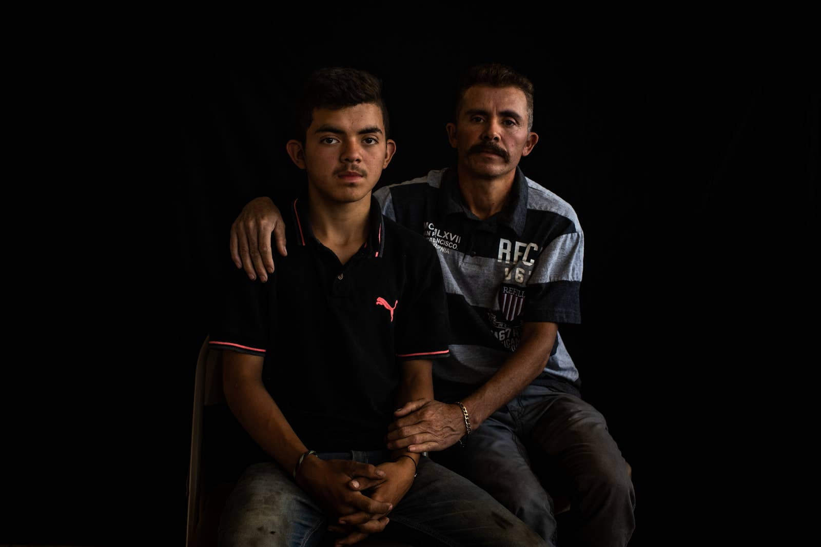 A man sits beside his son and has an arm around him