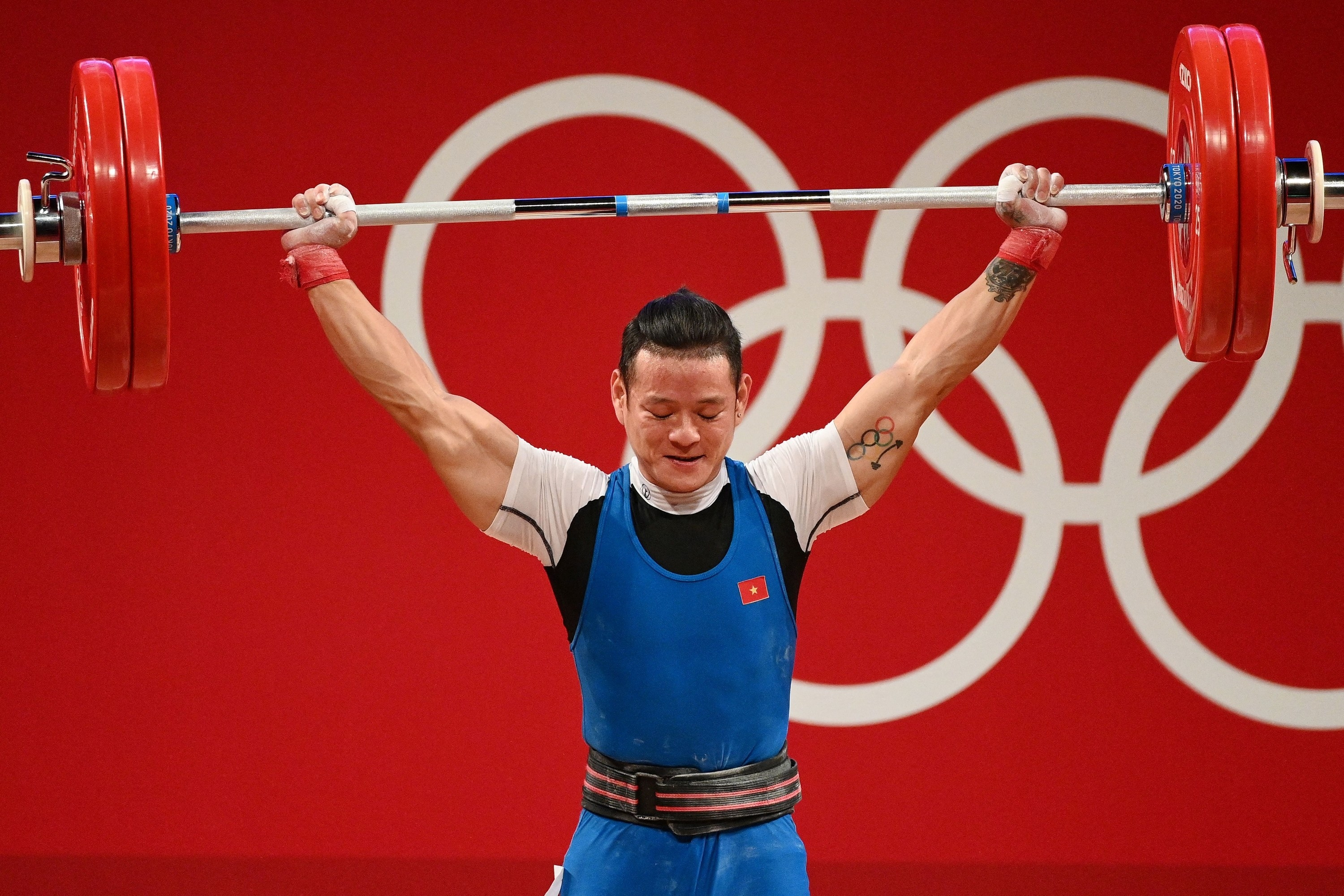 Olympic weightlifter holds barbell overhead in competition.