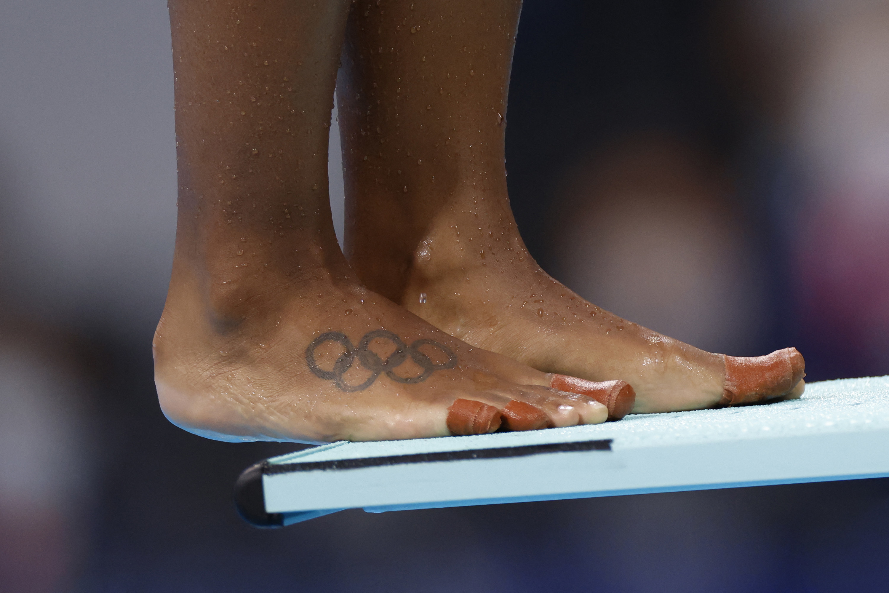 Close-up of swimmer's tattooed feet on a diving board