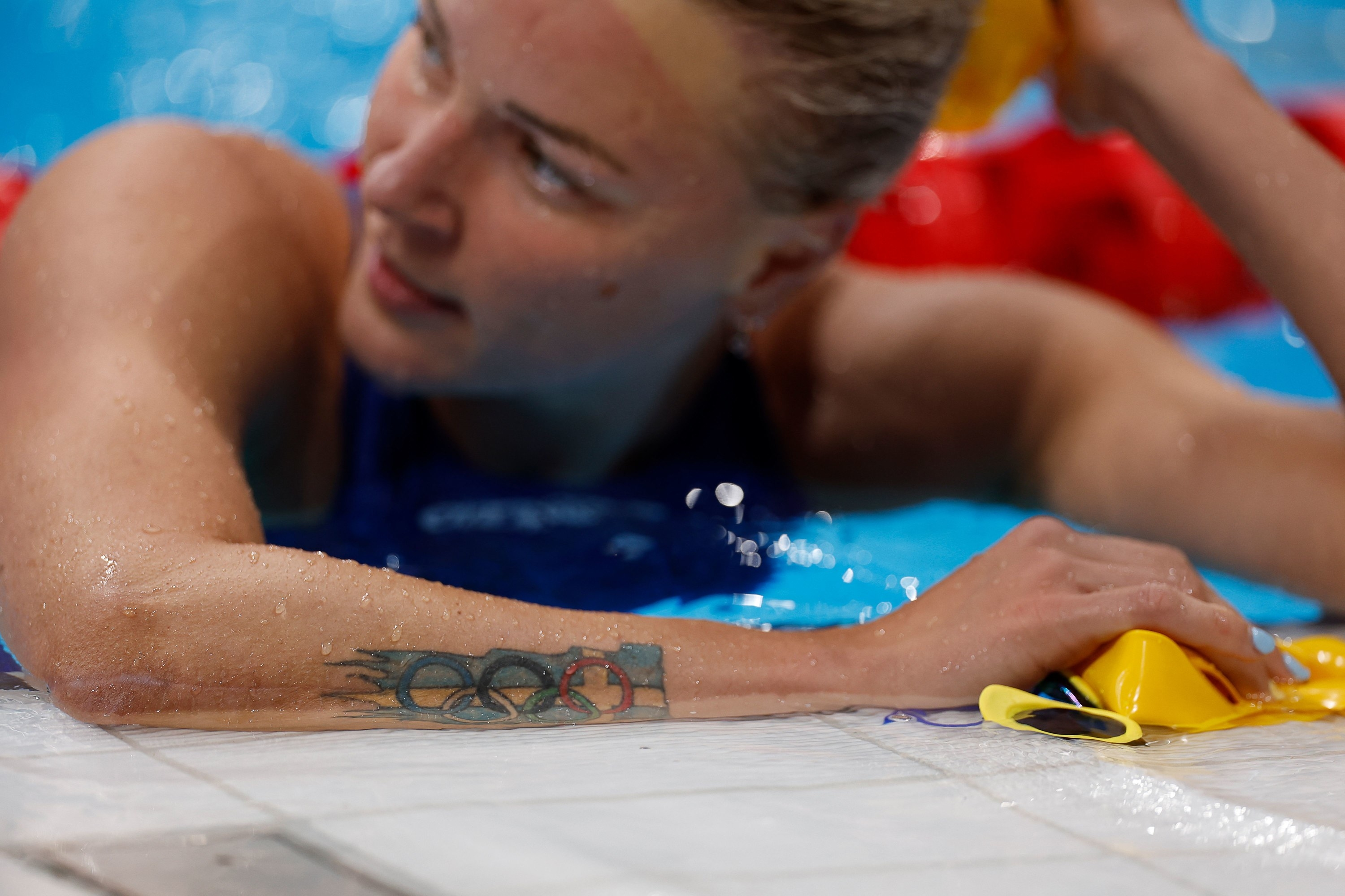 Female Olympic swimmer rests on side of pool.