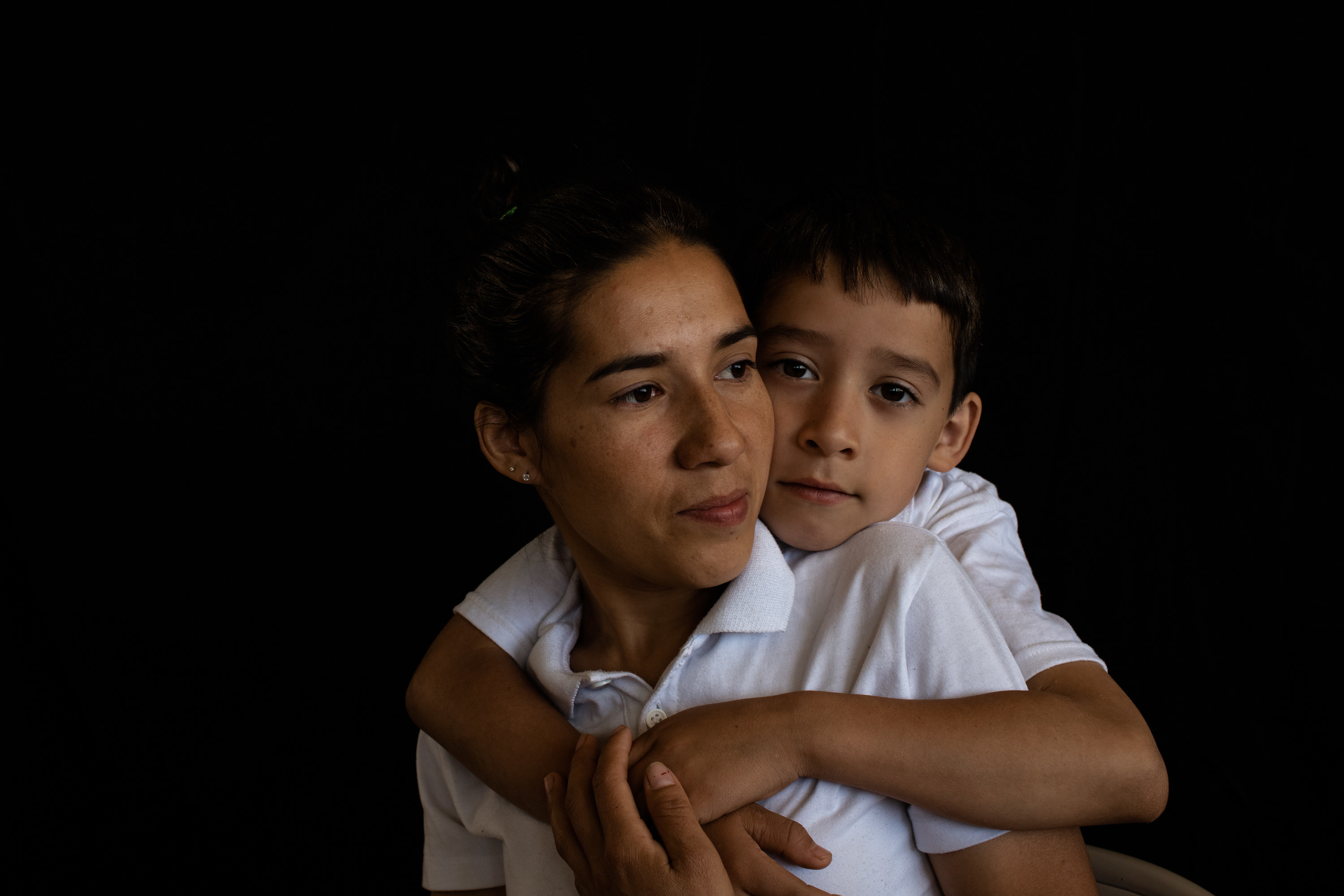 A sitting woman is held by her son, who stands behind her and embraces her